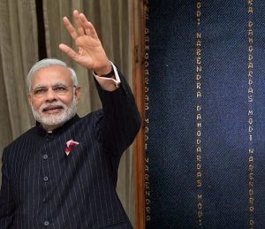 Modi wearing a suit with his name woven into it in gold pinstripes